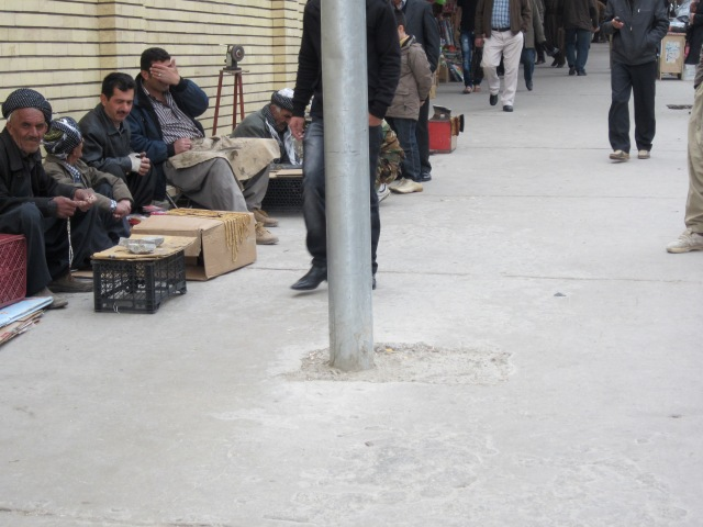 Outside the mosque in the bazaar, men sit with jackhammers, shoe shine kits and various things